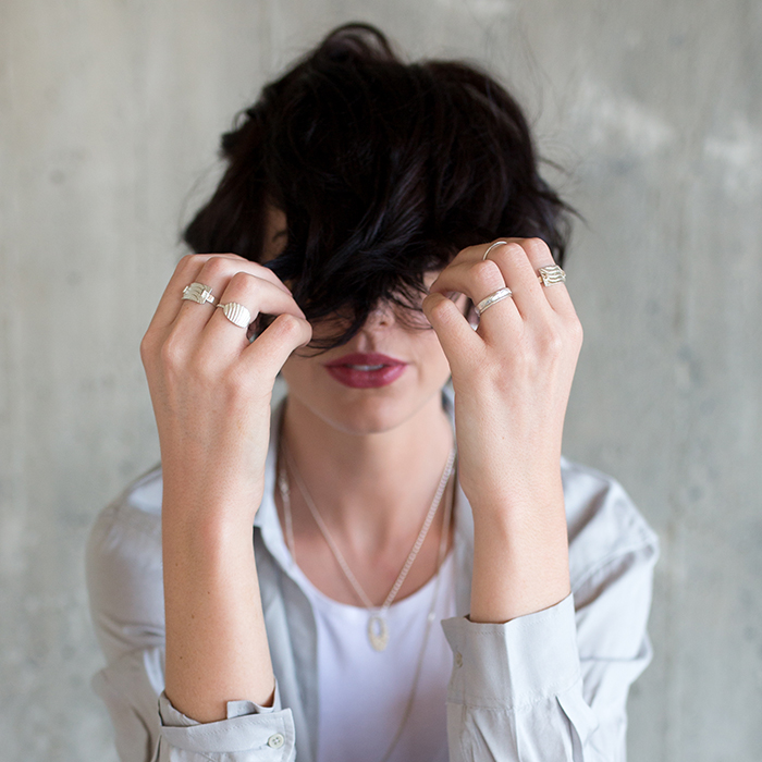 Model wearing Foundri rings with hands in front of face