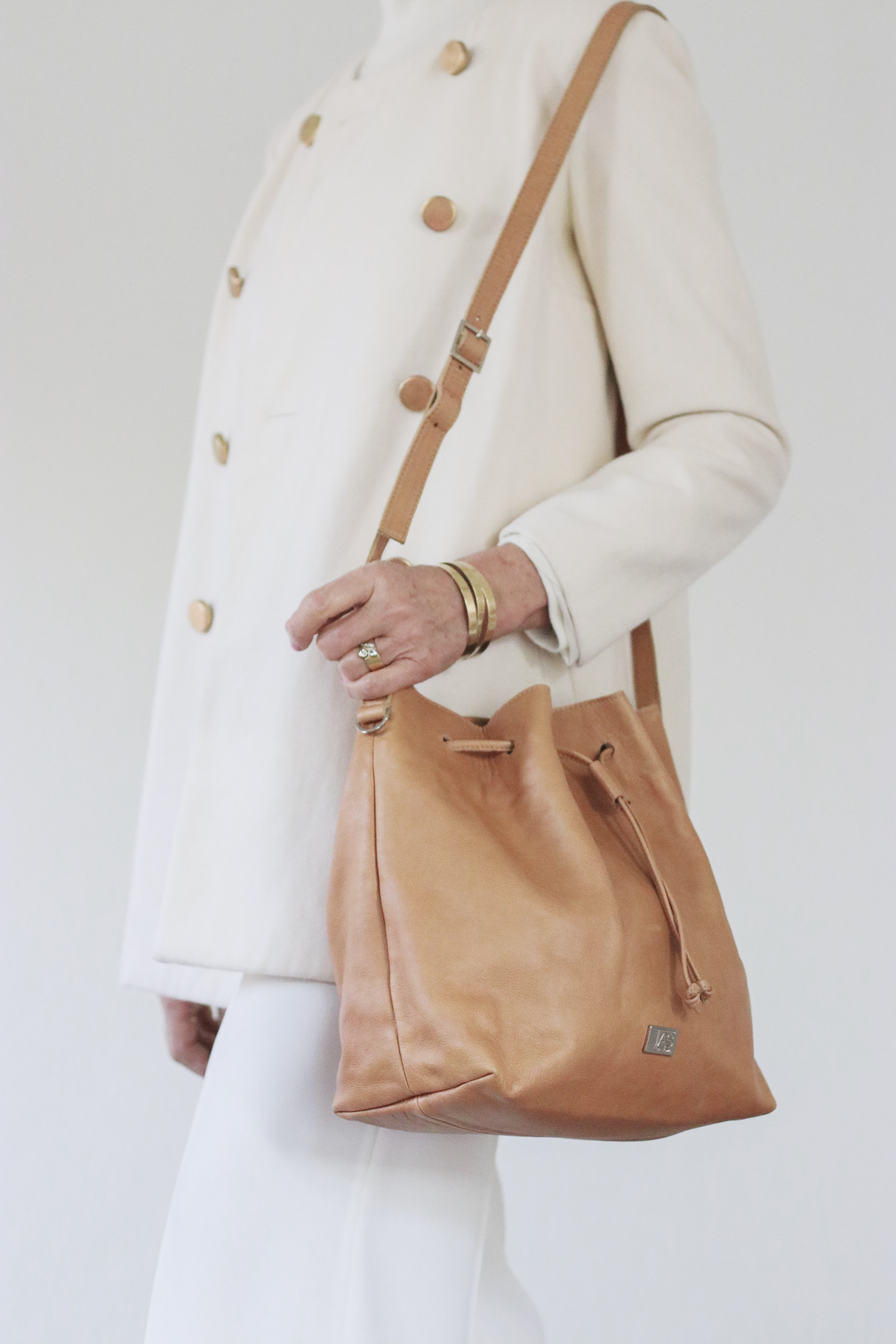 A soft leather bucket bag with an adjustable sling to carry all your essentials in a stylish way. Lined with grey cotton fabric, One zip side pocket inside.  Size 30 x 28 x 14cm