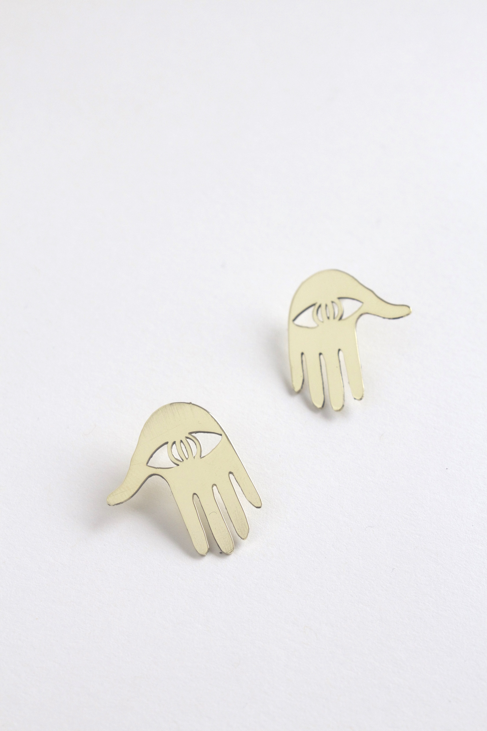A cut-out hand/eye earring.
