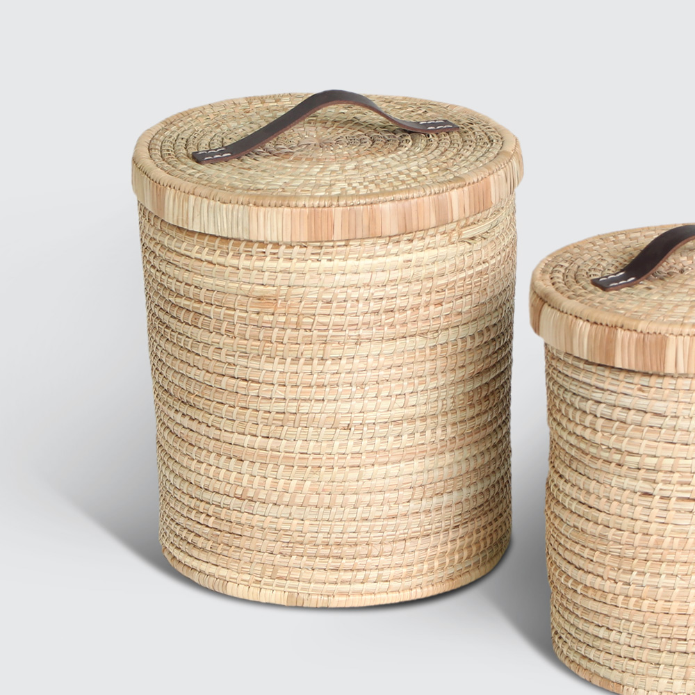 A strong, round storage basket. Sturdy base, tidy look with leather-handled top cover. Woven with Palm. Great for things like toys, accessories, or as a general tidier.