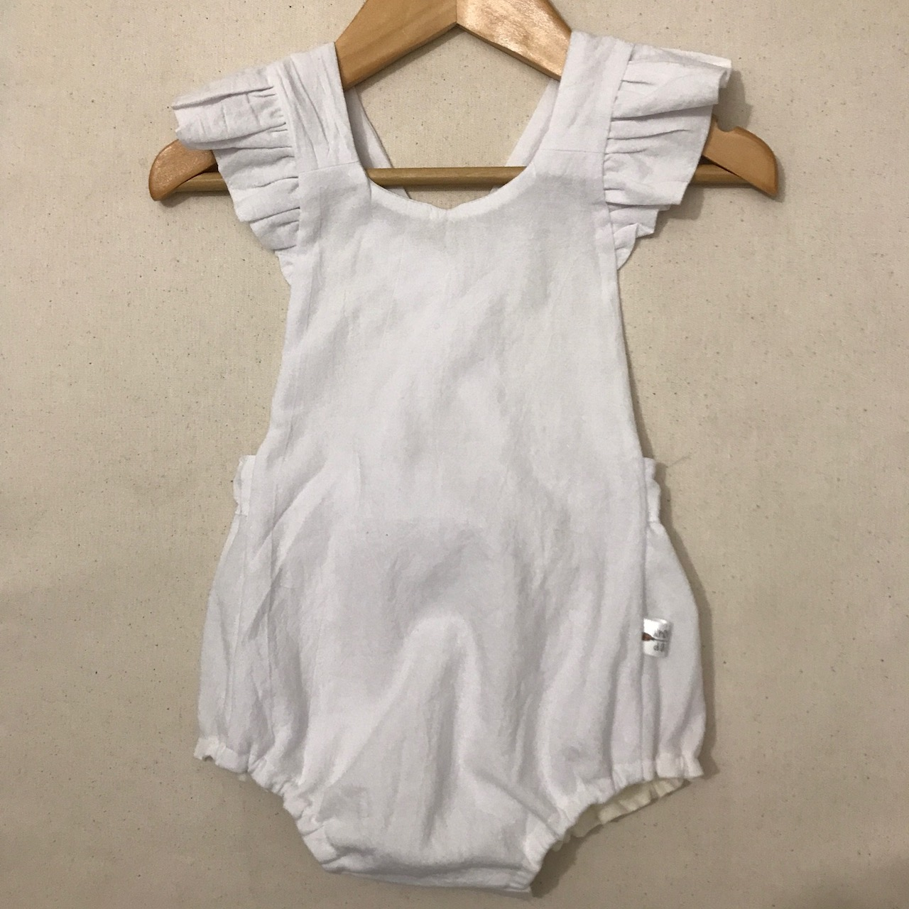 Oh goodness, this little summer romper is just too adorable!. Its criss-cross open back with frill detail will look oh so cute on your little one.  Features:   100% cotton material (light to medium weight) - do not tumble dry buttonson the inner side of backpiece to attach straps to bodice (2 height adjustments for strap length) 3 snap closures at crotch elasticated waist and leg piecesfor the perfect fit