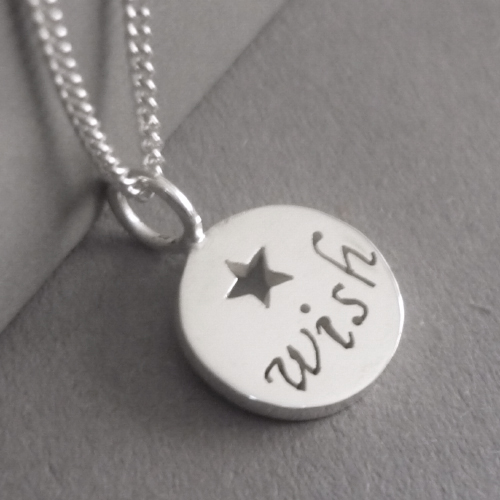 Sterling silver tiny disc pendant, with hand-cut lettering (wish) and a little star.