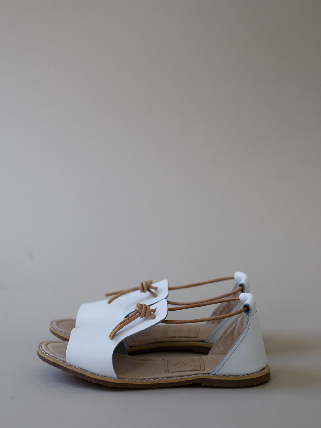 Fundo· Swahili translation :knot  The break-out star of summer 2017 is undoubtedly the FUNDO. Demure and carefully crafted, the FUNDO is the staple you return to time and again to balance your inner hipster and French fashionista. Elegant but edgy, these kicks will transition seamlessly between crisp mornings + sultry summer afternoons.   The Fundo is the first kid on the block from our summer 2017 offering: crafted from full grain leather with a soft insole for added comfort. A simple top-knot adds subtle detail and a rubber sole (for added grip) ensures its beauty equates its durability.