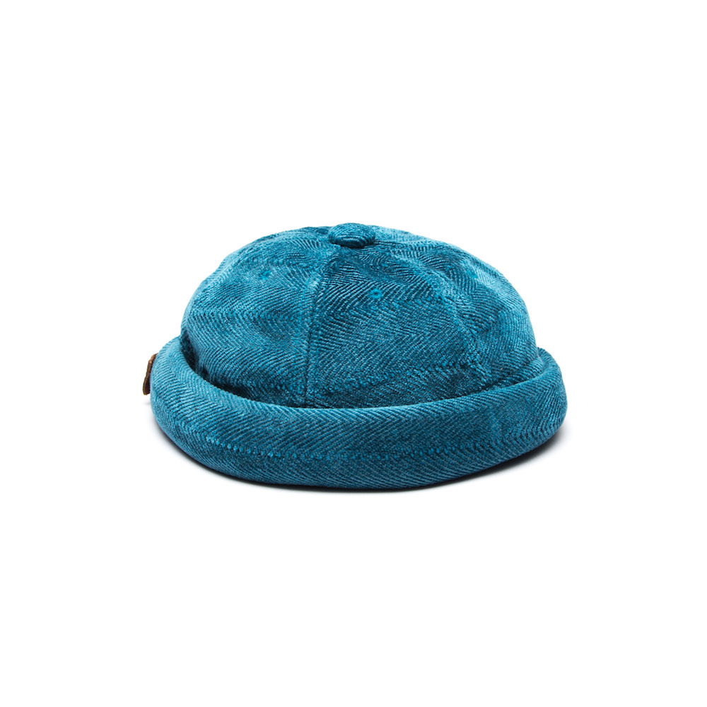Short cap that blends the key features of a beanie and a cap. Finished with an adjustable leather back strap. Cut from a luscious chenille/cotton throw milled in Plettenberg Bay, South Africa. 