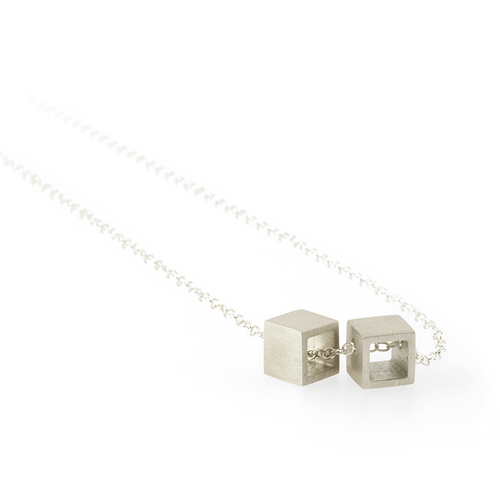Two dainty sterling silver open cubes dangle from a sterling silver chain. Each cube measures 6mm.