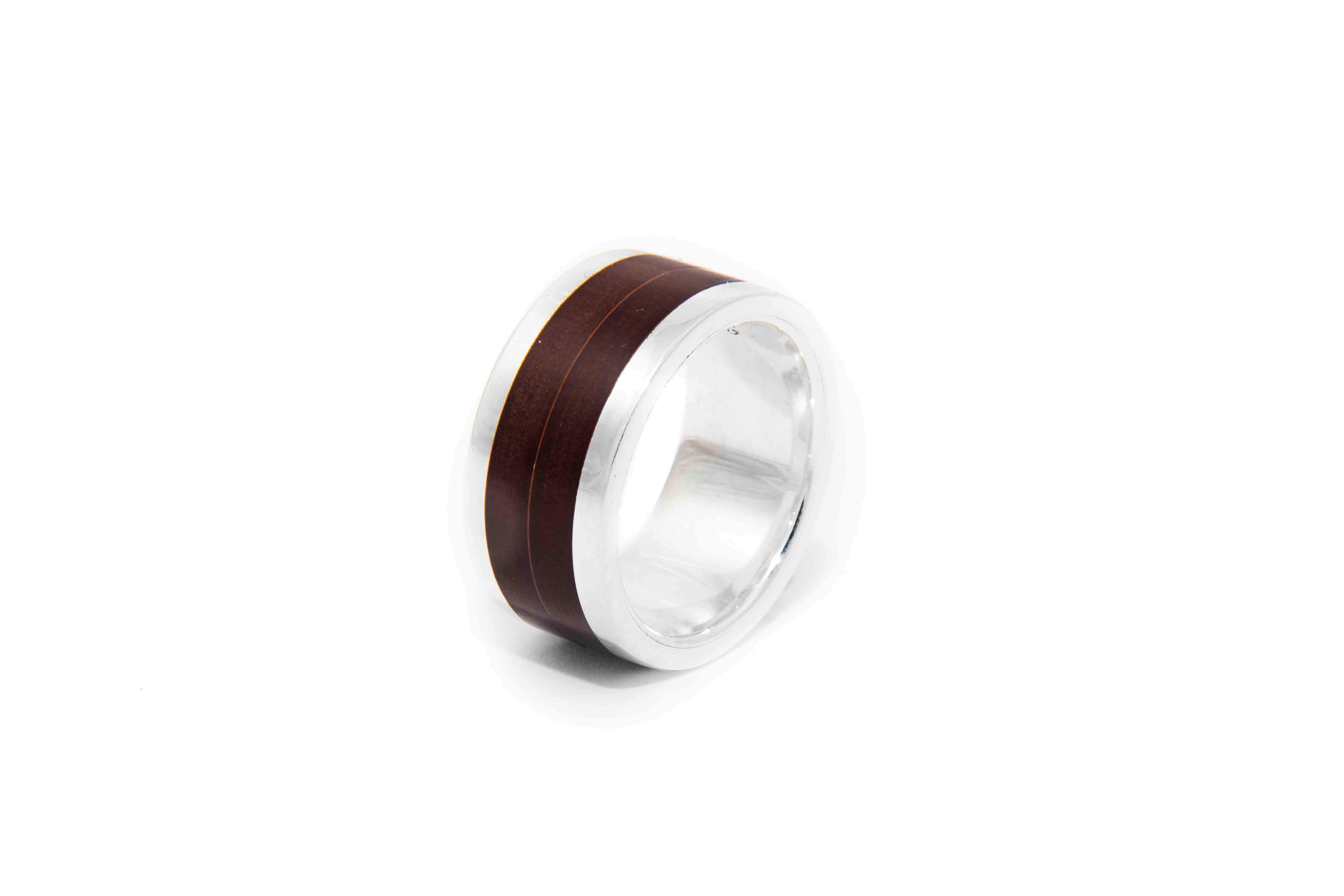 This minimal ring is handmade from sterling silver with a paper micarta inlay, with a minimal accent in the centre.