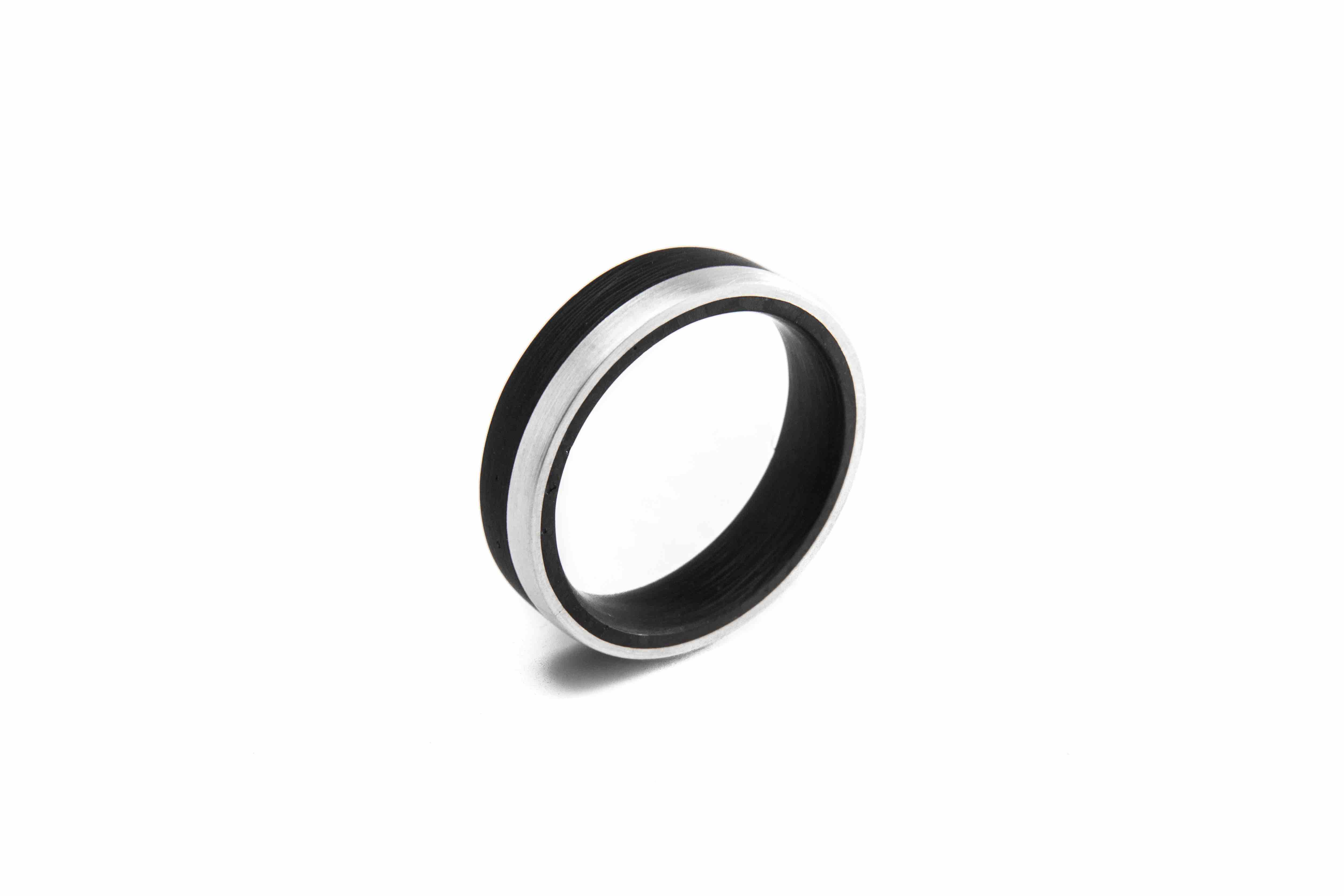 Machined Carbon Fibrewedding ring with fitted sterling silver inlay  Super light, Super strong, minimal contrasting elements.  This ring is 6mm wide though your personaliseddimensions are welcome.  Please let us knowyour ring size and required dimensions. Available in Matt or high polished finish.