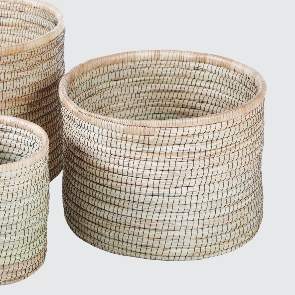 A round basket in a solid Palm Leaf woven with recycled tyre thread. Incredibly durable and sturdy. Great as pot plant holders, toy storage, or firewood.