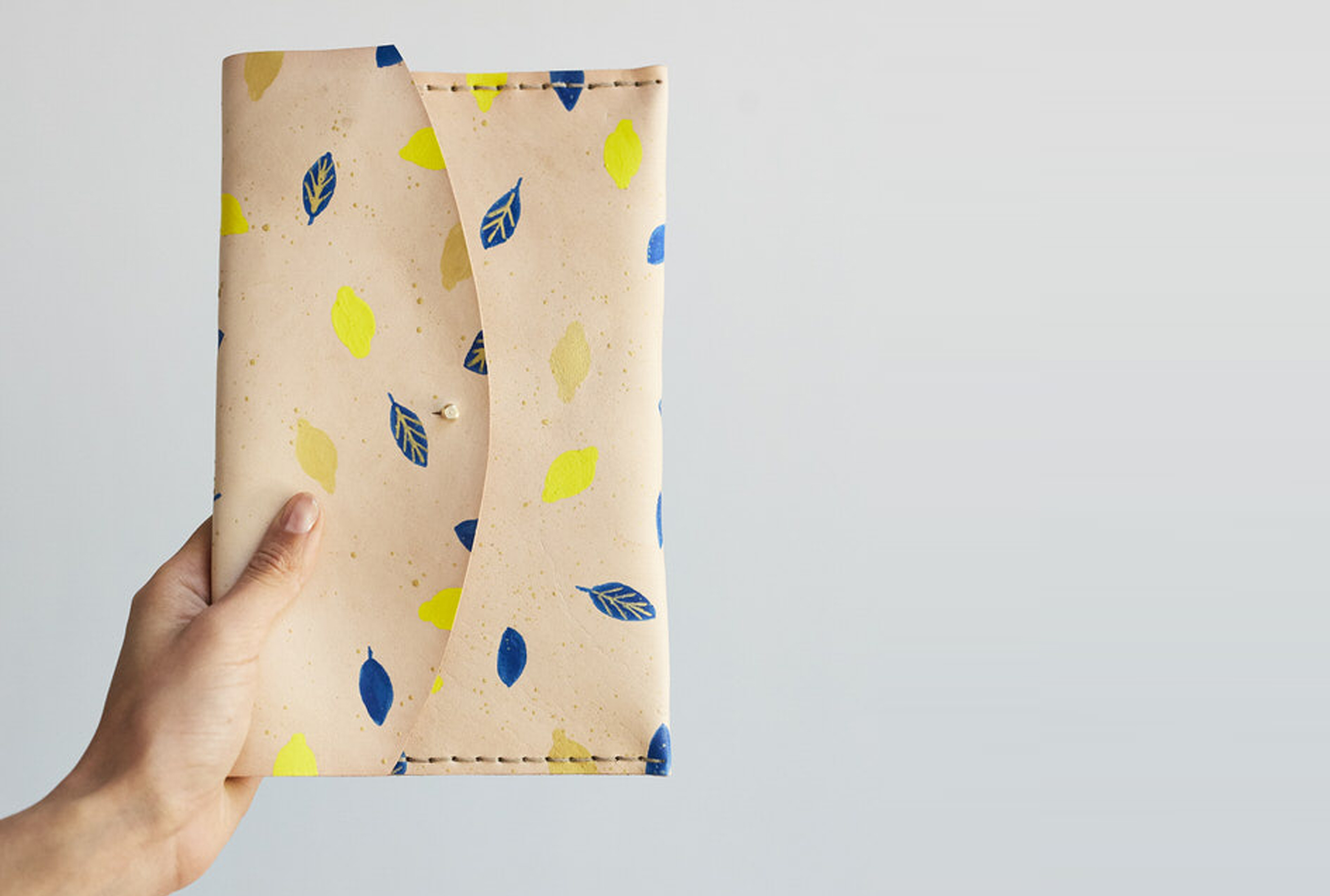The Lemons Clutch in oyster is hand crafted using locally sourced vegetable tanned cow hide. It is hand painted by Cape Town based artist Danelle Malan using a specially formulated leather paint. As the pattern is hand painted, please expect slight variations from product to product. 