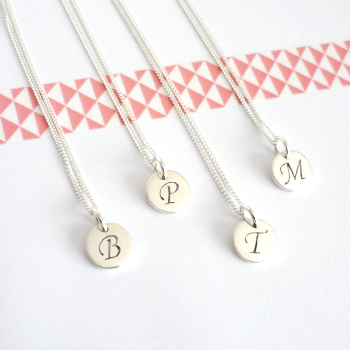 Dainty tiny little disc charms, with a cut out initial in the centre..
