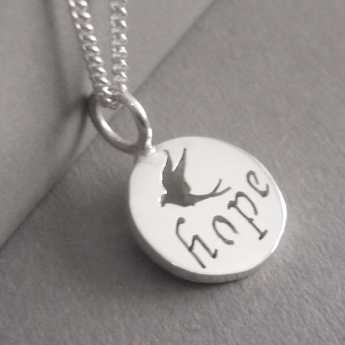 Sterling silver tiny disc pendant, with hand-cut lettering (hope) and a dainty flying bird.