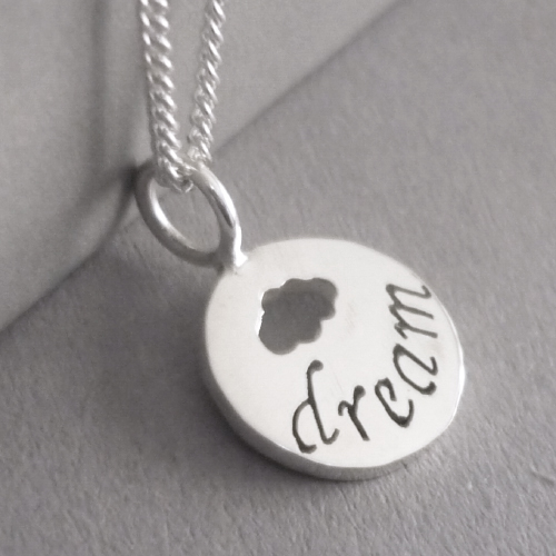 Sterling silver tiny disc pendant, with hand-cut lettering (dream) and a little cloud.