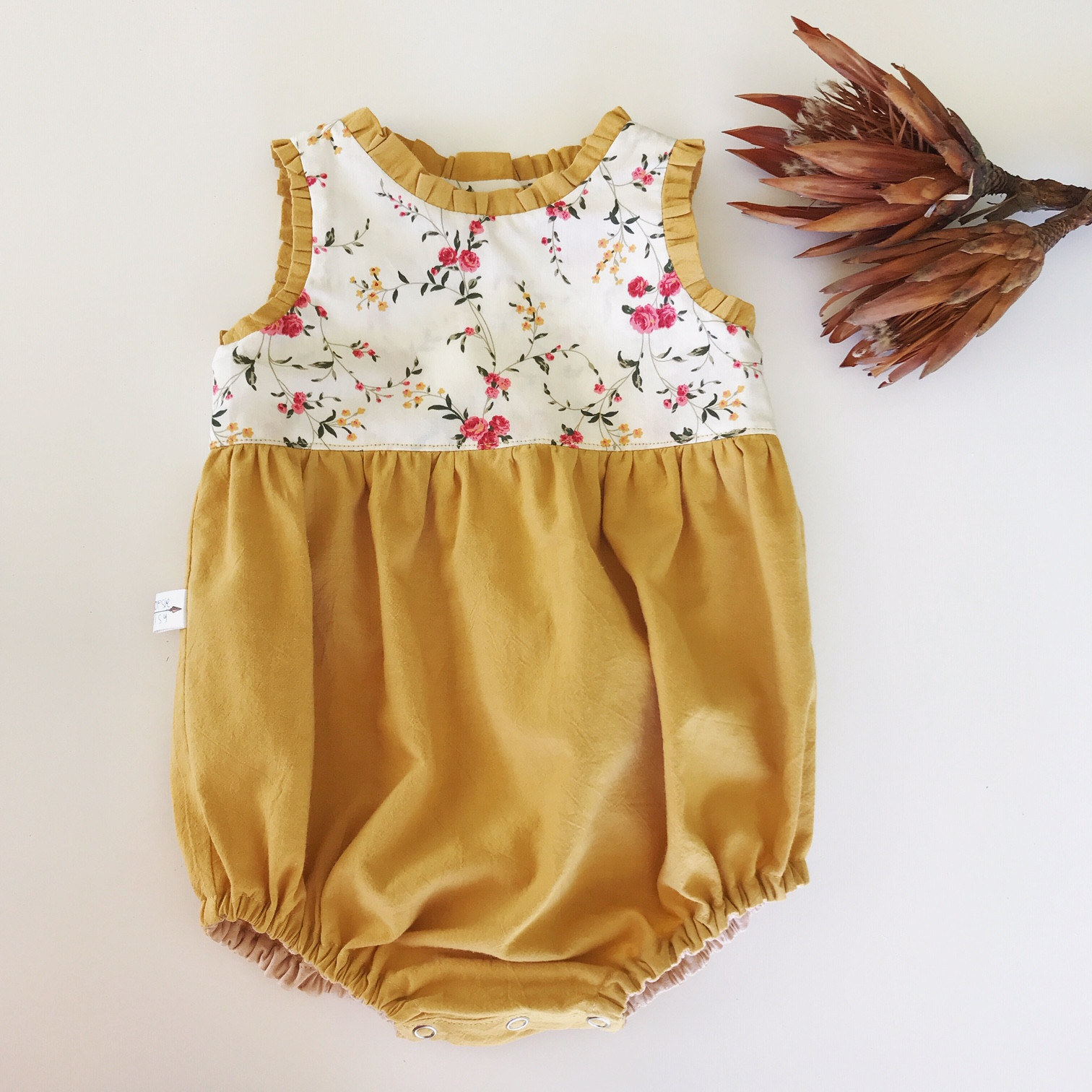 A new addition to our Autumn 2019 range. This romper is made with soft medium weight, mustard & floral cotton material. Cute ruffle accents along the neckline and arm holes. Button closure on the back bodice and snap closure at the crotch.  Pare this romper with a simple long sleeve vest and knee high socks and your little one will be oh so stylish.