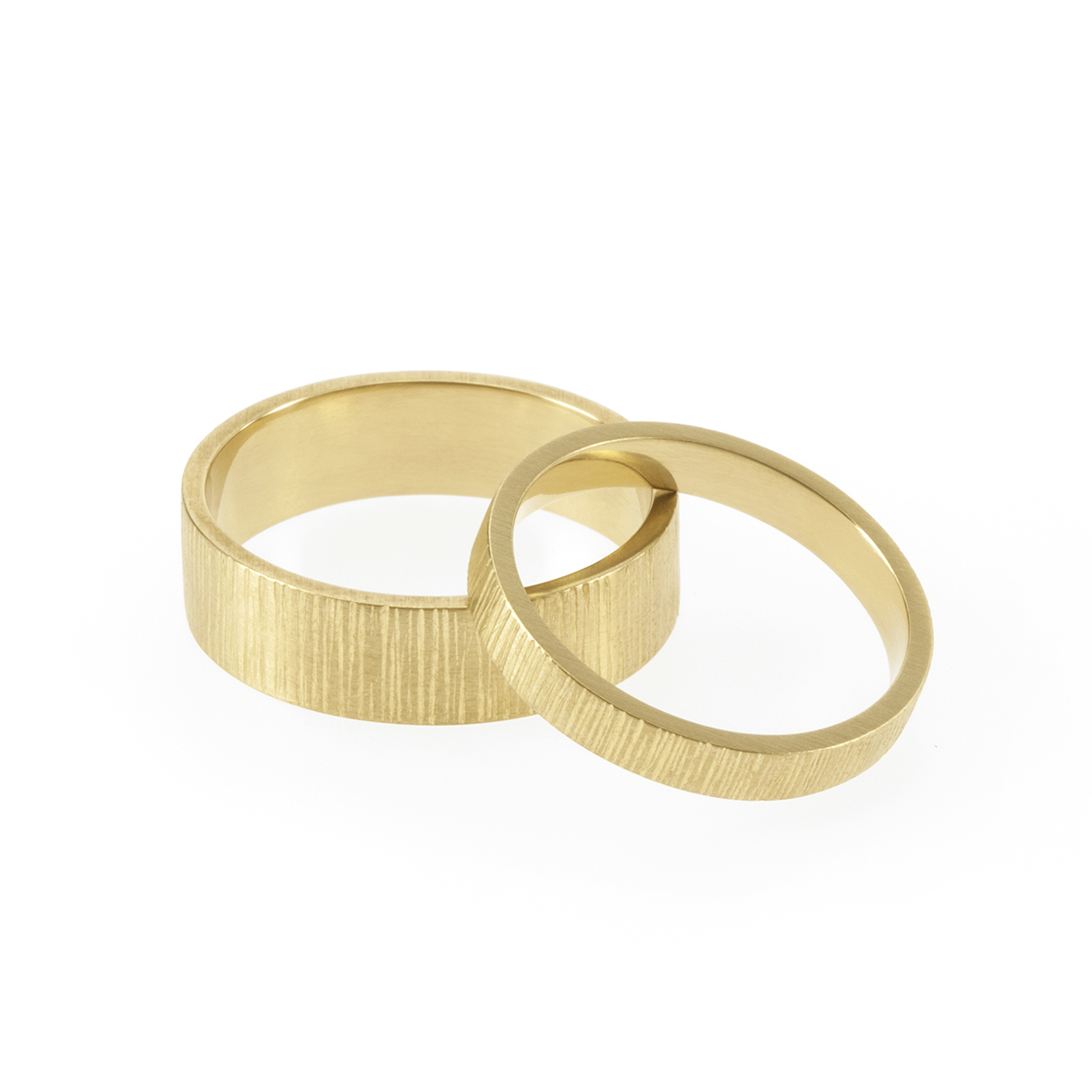 A union of geometry and organic forms, our flat profiled band with hand-carved vertical lines reminiscent of tree bark.