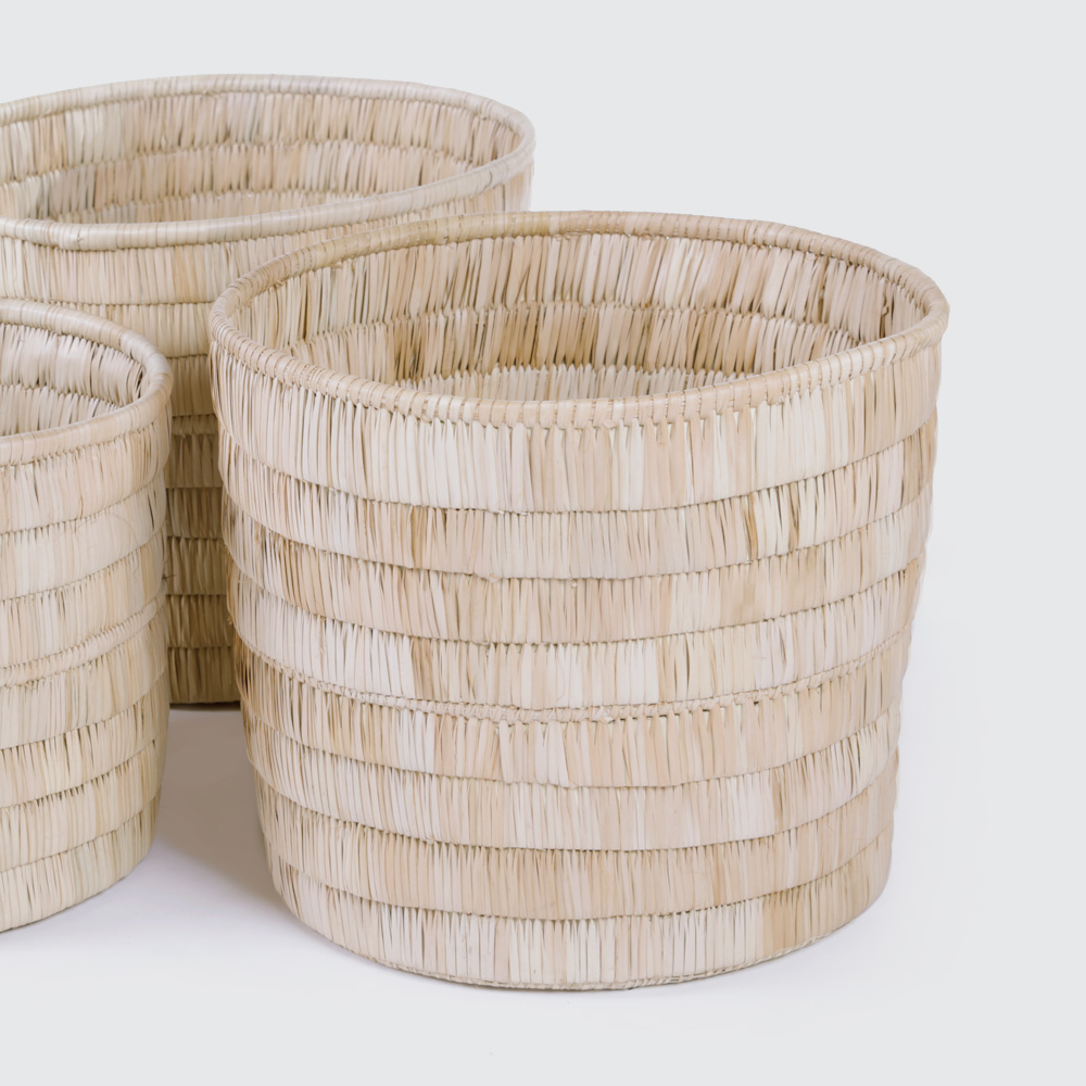 A round basket in a solid Palm Leaf weave with a thatch-style layered look. No handles, great for pot plants or to keep a spare throw.