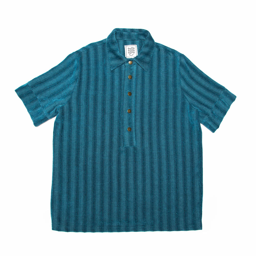 A classic box-shaped polo shirt. Finished with a straight hem and antique brass buttons. Cut from a luscious chenille/cotton throw milled in Plettenberg Bay, South Africa. 