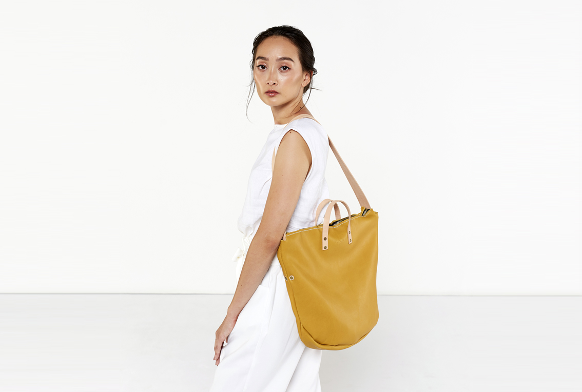 The Zip Tote in marigold is entirely handcrafted. A fresh new take on the tote bag, featuring a zipped closure and a removable shoulder strap. Can be worn without the strap as a soft work bag, or with them as a slouchy shoulder bag. 