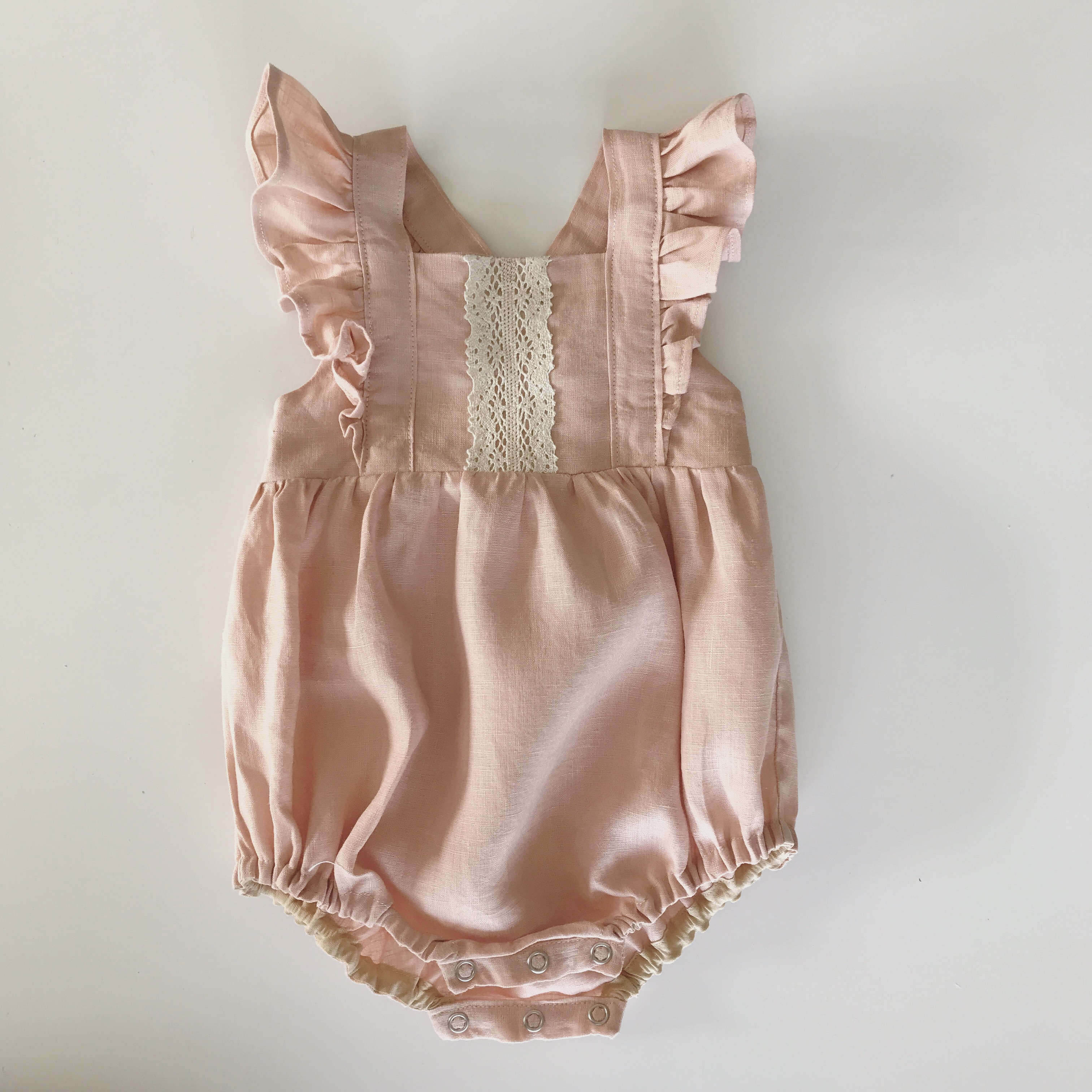 A beautiful vintage inspired romper, you will simply adore. Frill accented shoulder straps with button closure on back side of bodice. 2 height adjustments on straps.