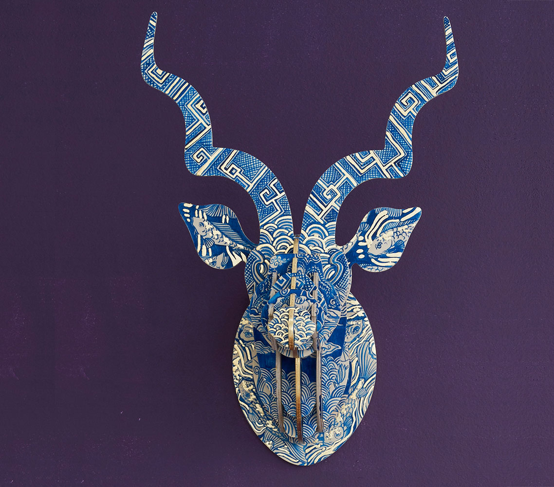 This beautiful Delft 'Koi Fish' Kudu sculpture, painted by Cape TownartistSharon Boonzaier, is inspired by the Far East's blue patterning used on European delft ceramics and then brought to the Cape by the Dutch settlers in the 1600s. All this infused with the beauty of the Japanese Koi fish.  The piece is finished with gold leaf and signed by the artist.  No one piece is the same and each unique head is an artwork to behold.  When you order one of these special pieces, you may receive the one in the photo if it is not yet sold, or Sharon will create a new one for you, but slightly different in order to keep each sculpture unique.  The sculpture comes flat-packed with clear instructions on how to assemble and hang as well as a story about the artist.  Sculpture Dimensions: MED: 62cm (h) x 41cm (w) x 38cm (d) Depth = wall to tip of nose  Weight:2.5kg  Cleaning & maintenance:  Dust with a cold hair dryer. Keep away from high humidity, direct sunshine and moisture such as steam. Not suitable for bathroom or outdoor installation.  Shipping:Cape Town R80, National R120,Outside of South Africa -R1100  Payment Options: South Africans: Please use Payfast International customers: Please use Paypal  We may have one ready to ship to you, or it may take 3 weeks for Sharon to paint you one. We'll let you know soon after you place your order.