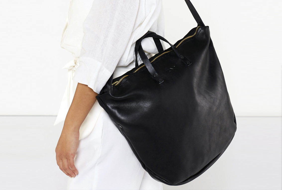 The Zip Tote in onyx is entirely handcrafted. A fresh new take on the tote bag, featuring a zipped closure and a removable shoulder strap. Can be worn without the strap as a soft work bag, or with them as a slouchy shoulder bag. 