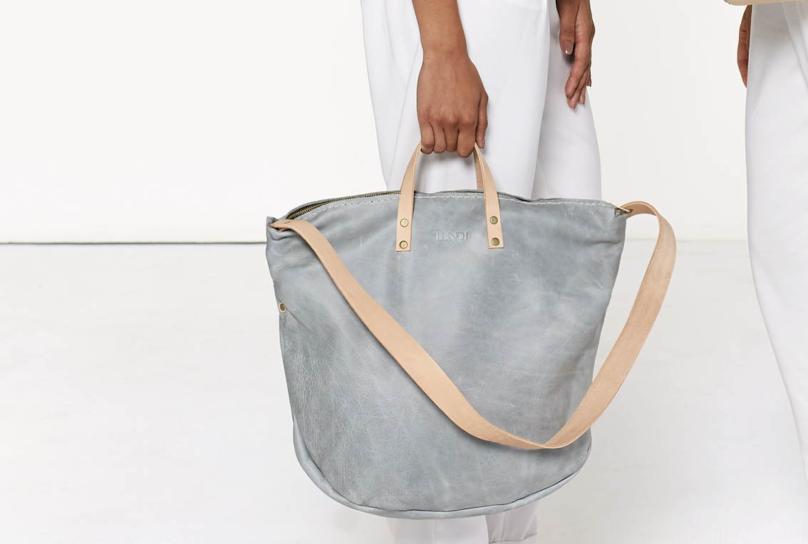 The Zip Tote in grey is entirely handcrafted. A fresh new take on the tote bag, featuring a zipped closure and a removable shoulder strap. Can be worn without the strap as a soft work bag, or with them as a slouchy shoulder bag. 