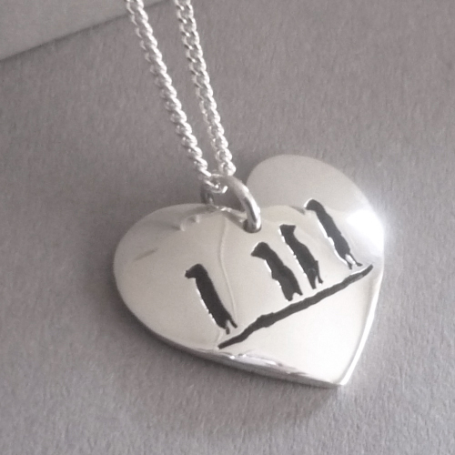 Domed heart pendant with cut out little meerkats.
