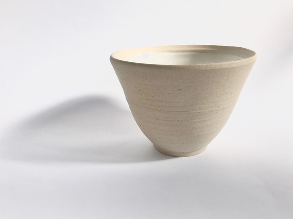Stoneware bowl with white glaze.  Each piece is hand thrown on the wheel by Liv and is intended to be used, seen and enjoyed in daily life as a reminder to always keep the earth close to us.  Hand washing your one of a kind piece is recommended.  As each of our ceramic pieces are handmade and unique, there may be slight imperfections.    Dimensions    Width Height Depth   11.7cm 8.5cm 7.7cm