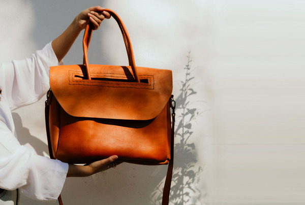 TheHeirloom Carryall in ochre is lovinglyhand stitched and made to last a lifetime. It is made with locally sourced leather and lined with canvas, and has one internal divider.  It is made with vegetable tanned leather and hand dyed. It is hand stitched and features a long detachable shoulder strap and rolled handles.  Dimensions: L 36cm x H30cm x W 7cm  Please note that all products are made to order and can take between 7 and 14 days to finish before shipping. Once your order has been shipped we will send you the waybill number for tracking purposes. We use Dawn Wing couriers for deliveries within South Africa. For international orderswe use DHL. Please note that all customs fees are to be covered by the receiver.  Ilundi products aremade with the finest quality materials available. Any irregularities in the colour or in the grain are normal characteristics of natural leather. Leather items may have wrinkles, scars or scratches, that are an inherent quality and natural beauty of the hide.