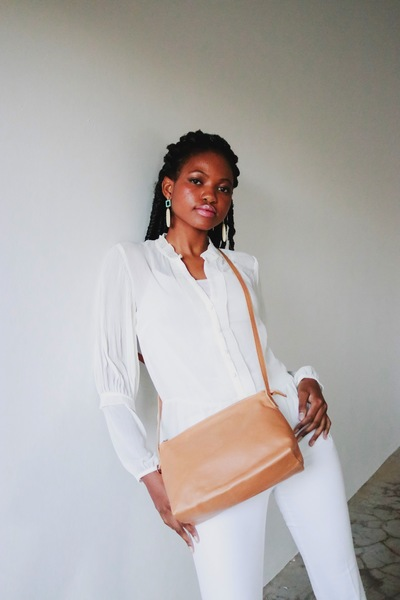 A simple sling bag with a triangular shape from the side. Great to grab-and-go. Lined with Shweshwelining and one inside zip pocket. The sling is adjustable.  Available in Caramel and Black  Size 25cm x 17cm x 10cm.