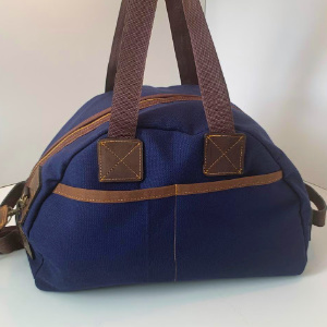 An overnight sized duffle bag which can hold a substantial amount. Side pockets provide space for wallets, phones, magazines etc.  We will personalise your bag if that is required. Send us an email at info@houndslowhandmade.com with the name required.  Pure quality and unique style.  Dimensions:45cm Long x 28cm High x 26cm wide  Materials:510gsm canvas and leather trim  Colors:Navy Blue, Olive Green, Gunmetal Grey  Lead Time:Ships within 3 working days  Delivery Fee: Flat Rate R100 countrywide OR Collect in Claremont, Cape Town