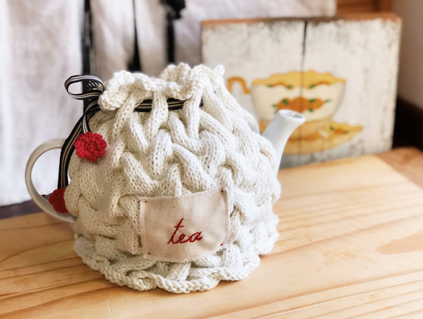 "A touch of nostalgia to add class to your tea party - or simply for the sake of enjoying something beautiful at home. Hand-knitted tea cosy, finished with embroidered word ""tea"" or ""tee"" in Afrikaans and an elegant drawstring with crocheted flower detail.