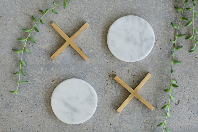 A set of 4 coasters - 2 brass plated crosses and 2 marble circles. 