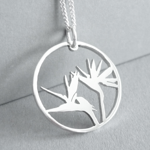 Sterling silver hand-cut strelitzia in circle pendant, on longer 55cm chain.