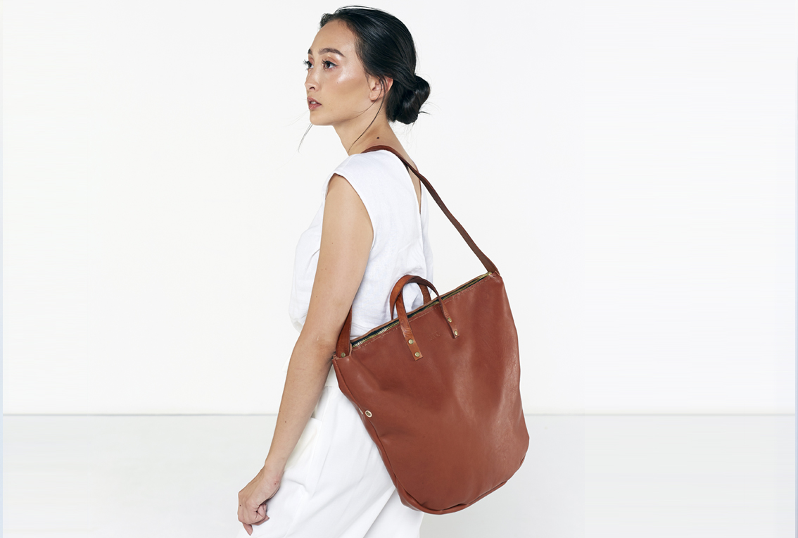 The Zip Tote in tan is entirely handcrafted. A fresh new take on the tote bag, featuring a zipped closure and a removable shoulder strap. Can be worn without the strap as a soft work bag, or with them as a slouchy shoulder bag. 