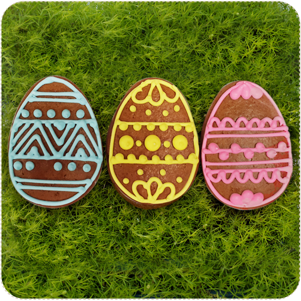 A set of three decorated easter egg shaped biscuits, in three vibrant colours.