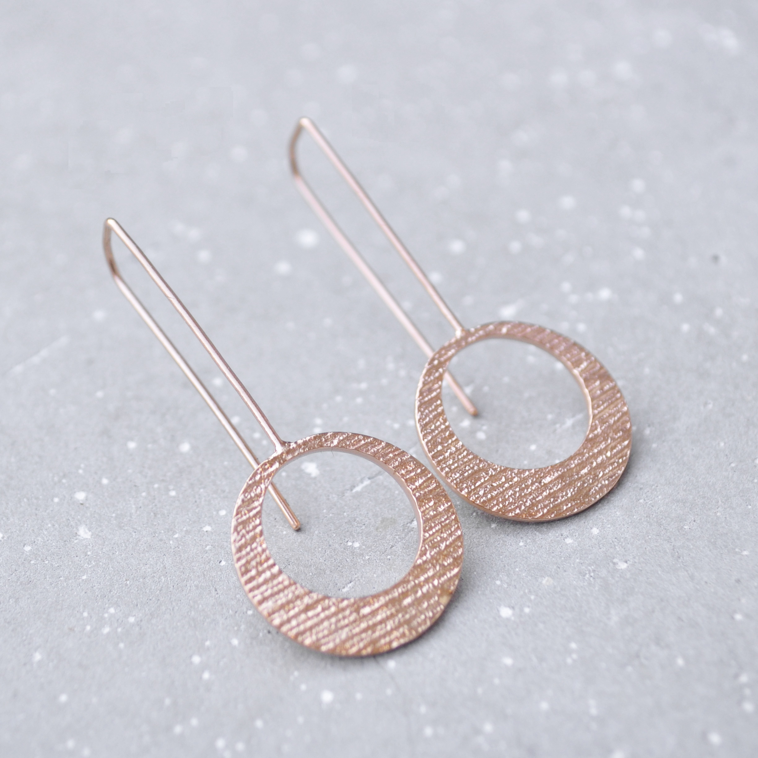 This trendy pair of Hollow Disc Jenna earrings is made of Sterling silver and plated with Rose Gold. This design is available in coco or leaf texture.