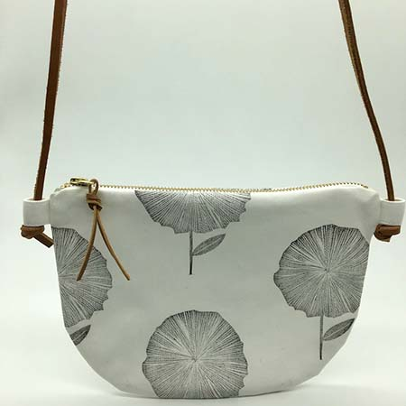 """The flower cross body sling is a classic handcrafted addition to your wardrobe. It features hand block printed cotton with a genuine leather adjustable strap, a gold zip and genuine leather tag.    Size: W 25cm (9.8"""") x H 19cm (7.5"""")  Hand block printed 100% white or oatmeal cotton, with a 100% white cotton lining.  Machine sewn with a gold YKK zip closure.  Genuine leather adjustable strap and zip tag.  Cold wash with like colours and a mild detergent with leather removed. Steam iron while slightly damp.  Includes bag only and not the other items used in the photographs.  Made by hand in Cape Town, South Africa"""