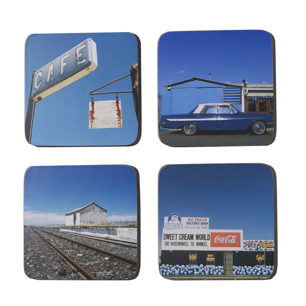 Under a blue sky, a cold beer in your hand, another day in Africa. A set of four coasters, cork-backed, heat resistant and wipeable with a damp cloth.