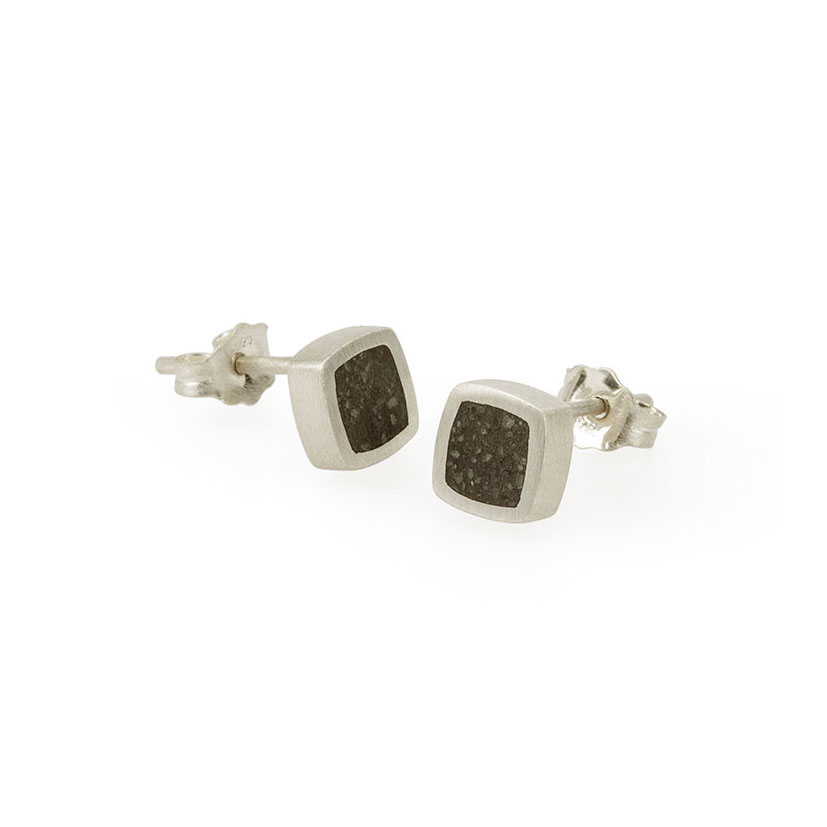 A pair of silver asymmetrical studs with concrete inlays. Each stud measures approximately 6.6mm square with a thickness of 2.7mm.