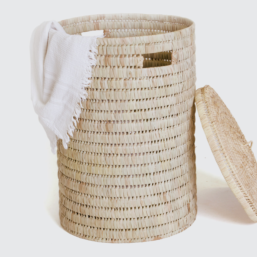 A sturdy, round laundry basket with a broader weave. Comes with small side handles and lid. Woven with Palm.
